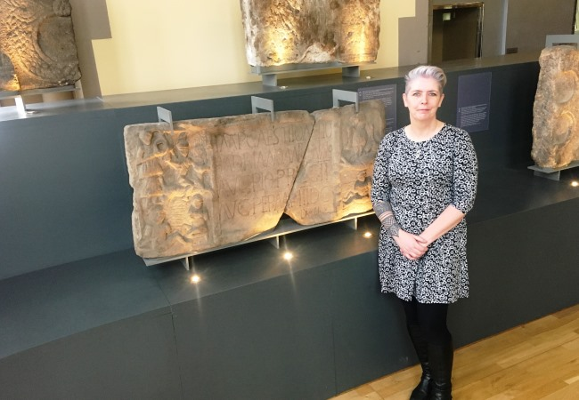 Dr Louisa Campbell with the Summerston distance stone at The Hunterian Museum