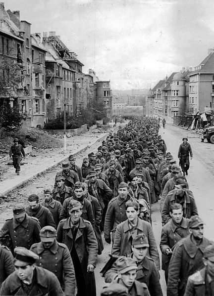 "Prisoners of war. Original Title: ""The endless procession of German prisoners captured with the fall of Aachen marching through the ruined city streets to captivity."""